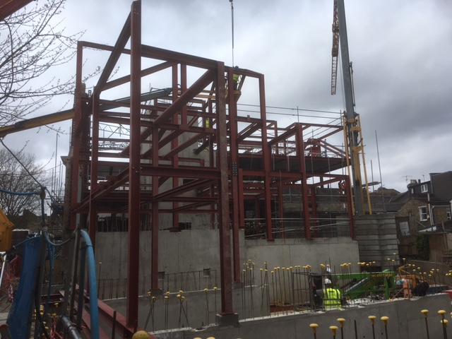 an image of a crane erecting the steel structure of a building
