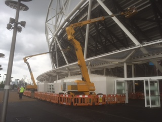 an image of two cranes erecting steel outside London Stadium