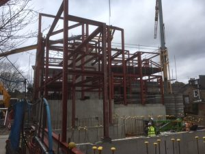 an image of a building during construction as steel is being moved into place
