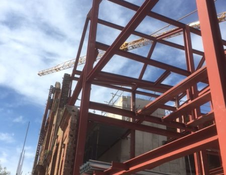 an image of a yellow crane through the gaps of red structural steel