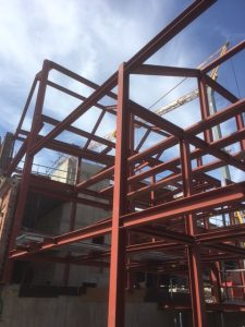 an image of the red structural steel making up the 'skeleton' of a building during construction