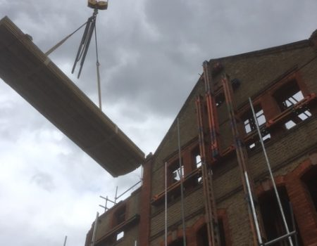 an image of a crane helping move parts of a building into place during construction