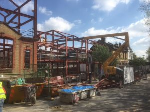 an image of an orange crane erecting steel beams into a steel structure
