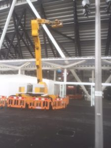 an image of a yellow crane-like machine lifting a piece of structural steel into place on the outside of West Ham Stadium