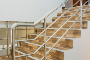 an image of a stainless steel bannister attached to light wood stairs