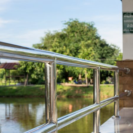 an image of a stainless steel guardrail attached to a column in front of a body of water