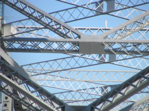 an image of a framework (perhaps of a bridge) made from structural steel latticed beams